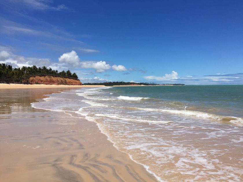 Praia com falésias, águas claras e mornas