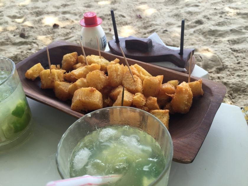 Porção de mandioca frita e caipirinhas