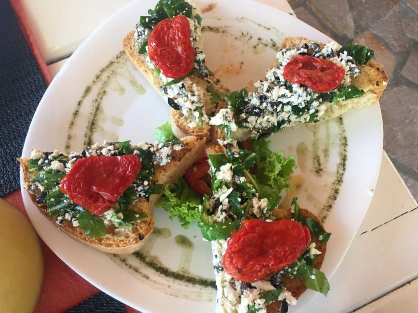 Bruschetta com ricota, azeitona, rúcula e tomate seco